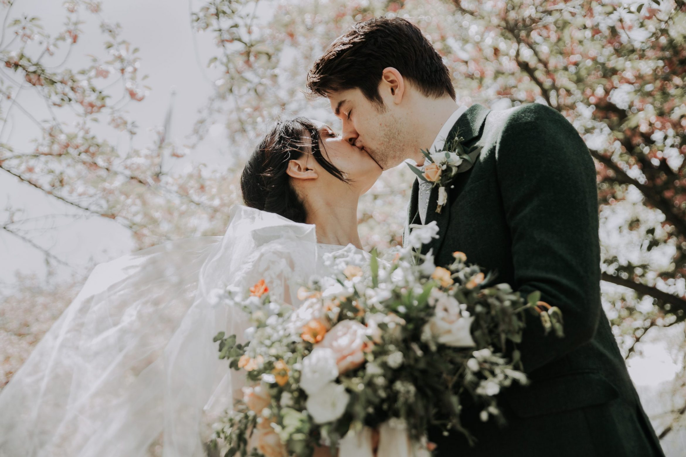 Bride and groom kiss at spring wedding