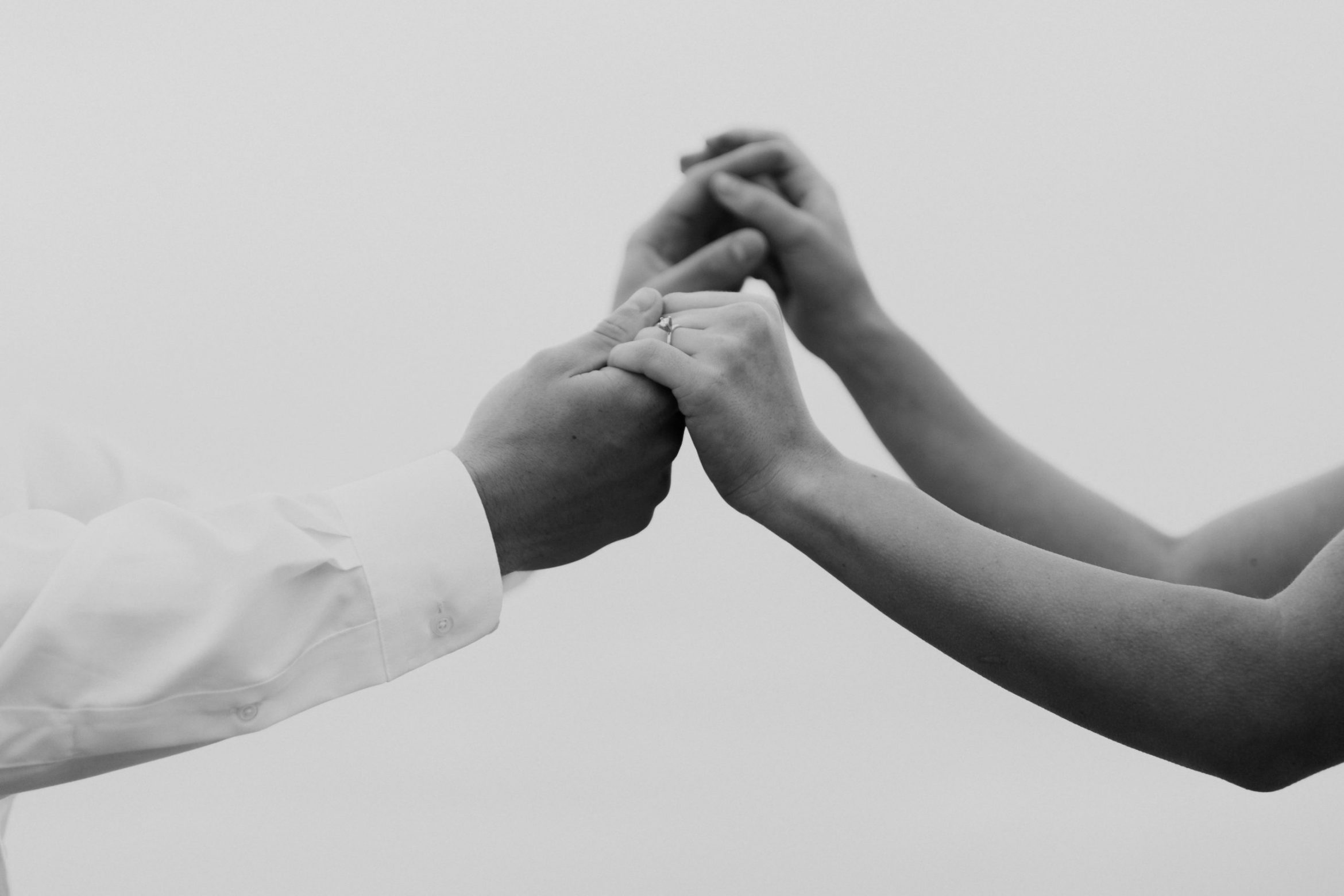 Couple holds hands in black and white image